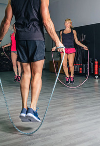 Trainer teaching exercises with jumping ropes to women