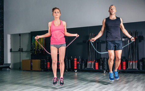 Young couple doing exercises with jumping ropes