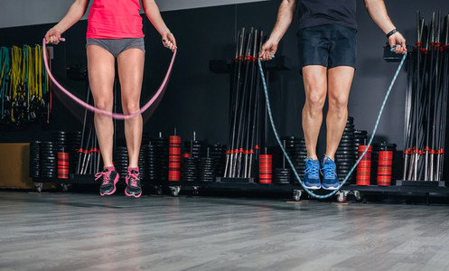 People legs doing exercises with jumping ropes