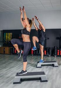 Couple doing exercises over steps in fitness center