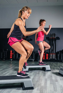 Women couple training over steppers in aerobic class