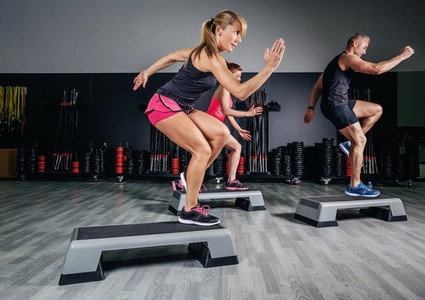 Woman trainer doing aerobic class with steppers in gym