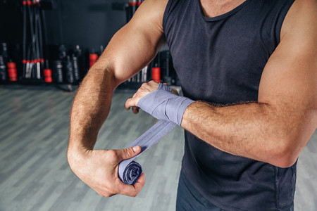 Man wrapping hands with bandages before boxing training