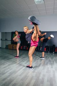 Women in a boxing class training high kick