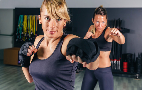Women training hard boxing in the gym