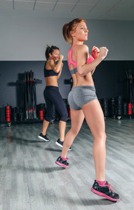 Women jumping in boxing training on gym