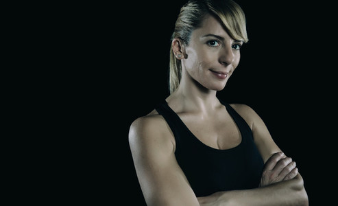 Athletic blonde woman with arms crossed over dark background