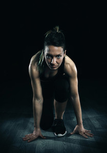 Athletic woman ready to run over dark background