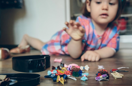 Baby girl playing with hair clips lying in the floor