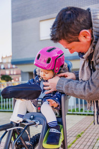 Father closing helmet to her daughter sitting in bike seat