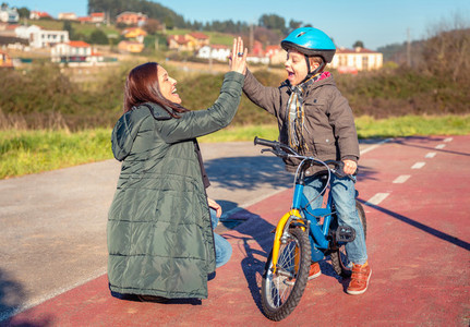 Mother and son giving five by success riding bicycle