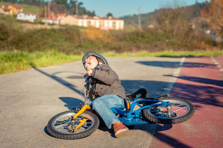 Boy crying and screaming after falling off to bicycle