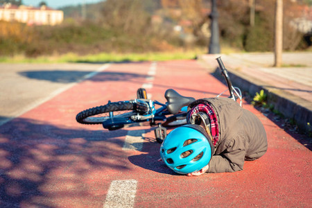Boy touching his head after falling off to bicycle