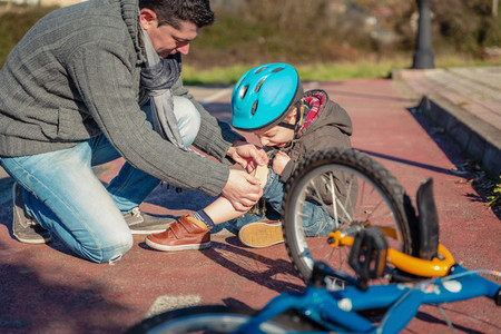 Father putting plaster band over knee injury to his son