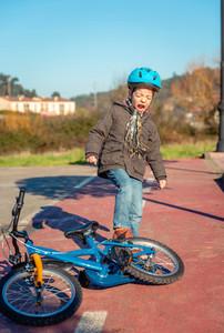 Naughty boy screaming and kicking his bike on ground