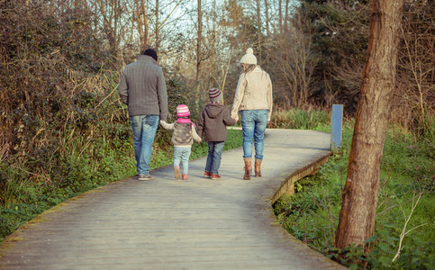 Happy family walking together holding hands in the forest