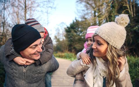 Parents giving piggyback ride to happy children outdoors