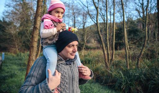 Man giving piggyback ride to little girl outdoors