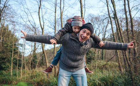 Man giving piggyback ride to happy kid in the forest