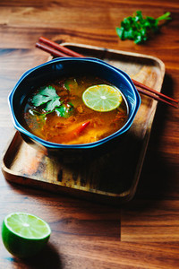 Vegetarian Thai Tom Yum soup with mushrooms on a wooden table