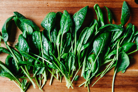 Top view of fresh spinach leaves on a wooden cutting board  Healthy vegetarian eating concept