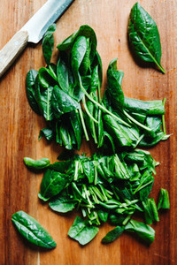 Top view of fresh chopped spinach leaves on a wooden cutting board  Healthy vegetarian eating concept