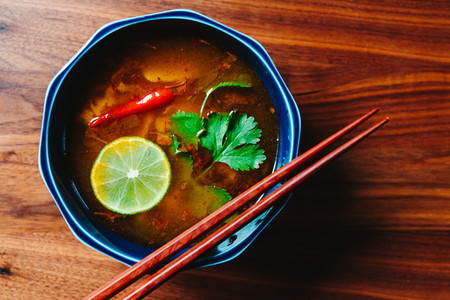 Top view of Thai vegetarian Tom Yum soup with mushrooms on a wooden table