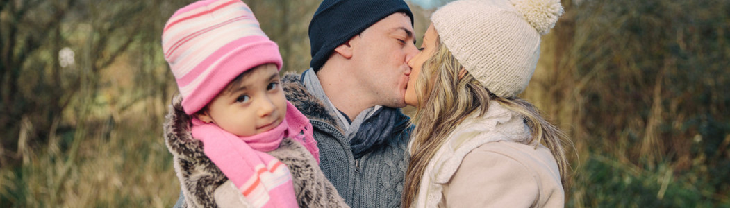 Happy couple with daughter kissing in the forest
