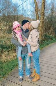 Couple with happy daughter kissing in the forest