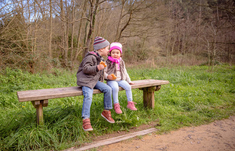 Boy talking to the ear of little girl sitting on bench