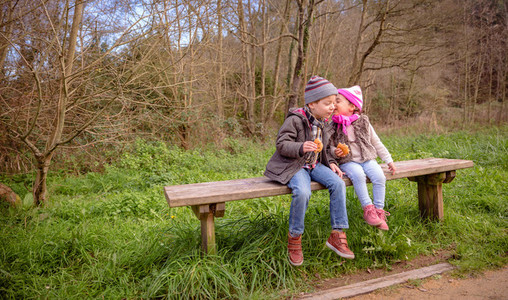 Little girl talking to the ear of boy sitting on bench