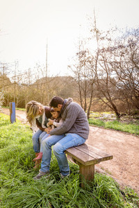 Man and woman playing with little girl sitting on bench