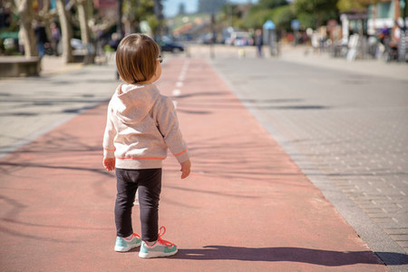 Little girl with sneakers standing over a city runway