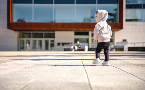 Little girl with sneakers and hoodie standing outdoors