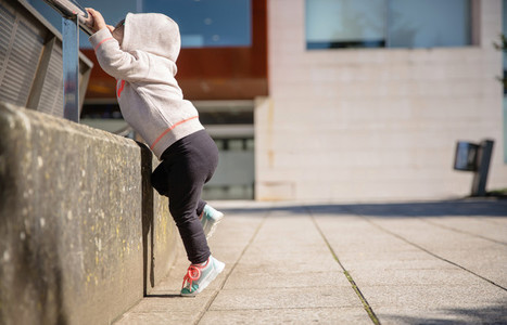 Little girl with sneakers and hoodie training outdoors