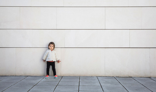 Little girl with sportive look posing over wall