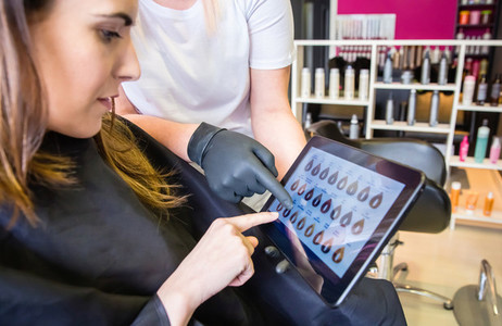 Woman choosing new color in hair dye palette on tablet