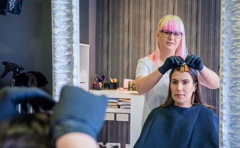 Woman with hairdresser looking hair dye sample in mirror