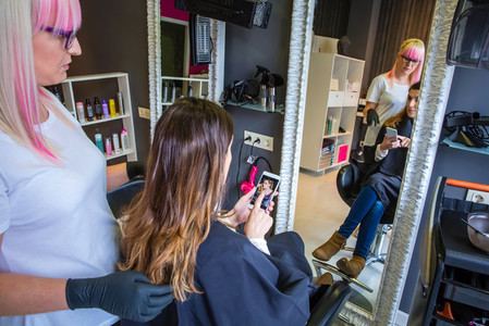 Woman showing hairstyle photo in smartphone to hairdresser