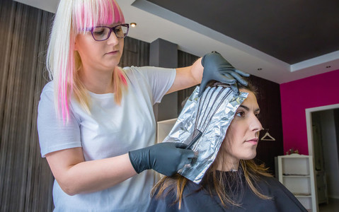 Hairdresser separating strands of woman hair with aluminium foil