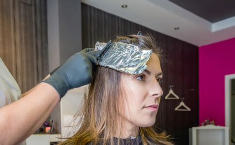 Hairdresser hands wrapping woman hair with aluminium foil