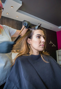 Hairdresser hands combing hair of beautiful young woman