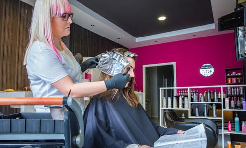 Hairdresser wrapping strands of woman hair with aluminium foil
