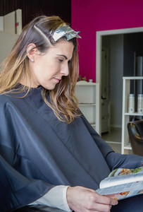 Woman reading a magazine while waiting with hair dye