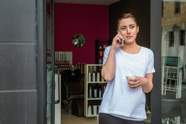 Hairdresser woman talking with smartphone in a coffee break