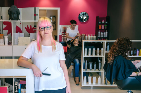 Woman hairdresser standing in hair and beauty salon