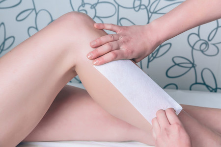 Beautician hands doing depilation in woman legs with wax strip