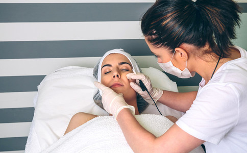 Woman getting rf lifting in her face in clinic