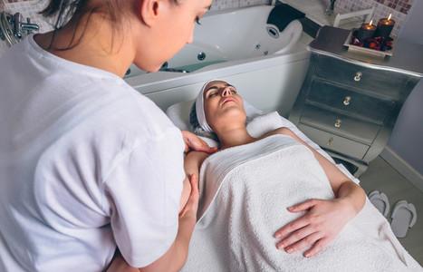 Massage therapist doing lymphatic drainage treatment to woman