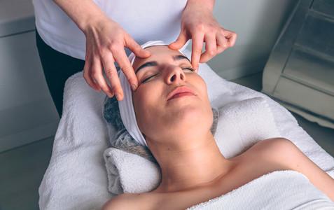 Woman receiving facial treatment on clinical center